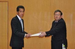 『千葉委員長から報告書を受け取る山口市長』の画像